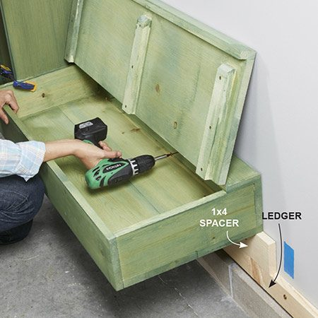 <b>Photo 11: Mount the bench</b></br> <p>Rest a scrap of 1x4 spacer on top of the temporary ledger to elevate the bench to the correct height. Set the bench on the spacer. Then drive screws through the back of the bench into the studs.</p>