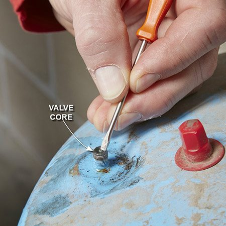 <b>Photo 4: Test for water at the air valve</b></br> <p>Unscrew the plastic cover from the air valve on the top of the tank. Use a small screwdriver to depress the air valve to see if water comes out.</p>