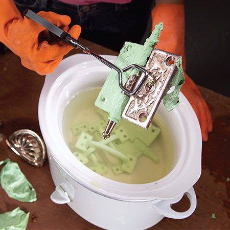 "<b>Strip hardware the easy way</b></br> <p>Got a lot of old hardware with paint on it? Fill an old Crock-Pot or other slow cooker with water and a couple of drops of dish soap. Then turn it on low and let the hardware ""cook"" overnight. The paint should practically fall off the next day. If it doesn't, gently scrub it off with a stiff plastic brush.</p>"