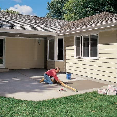 <b>Photo 1: Level the slab</b></br> <p>Screed floor leveler over low areas using a 2x4. Check the entire slab for low spots by laying a straight 10-ft. 2x4 on edge; any areas where the gap between the slab and the 2x4 is wider than 1/8 in. must be filled.</p> <p>Important: Nothing should cover isolation joints or fill expansion joints except caulk. If you get floor leveler or isolation membrane in the joint, scrape it off with a putty knife after it hardens.</p>