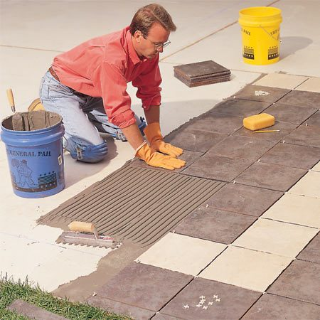 <b>Photo 3: Set the tiles in thin-set mortar</b></br> <p>Squish tiles into thin-set mortar adhesive applied with a 3/4-in. U-notch (rounded-notch) trowel. Twist the tiles back and forth slightly as you force them down. Your goal is complete coverage—that is, the space between the tiles and the membrane below should be completely filled with thin-set (no cavities to hold water and cause trouble). To allow enough space for grout, remove thin-set that wells up between the tiles or into expansion joints with a pencil or screwdriver. Clean thin-set off the surface of tiles with a damp sponge.</p>