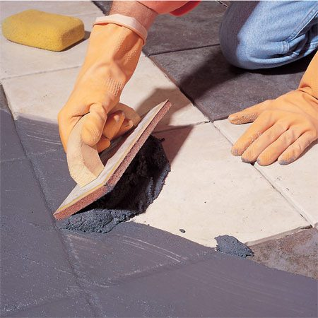 <b>Photo 4: Grout the tiles</b></br> <p>Push the grout diagonally across the tiles, holding the grout float at a 45-degree angle. Use a hard rubber float, not one with soft foam backing. To pack the joints densely, work the grout back and forth in all four directions. Then hold the float at nearly 90 degrees to the tile surface and scrape excess grout off the tile. Remove grout residue with a damp (not dripping-wet) sponge, rinsing it frequently.</p>
