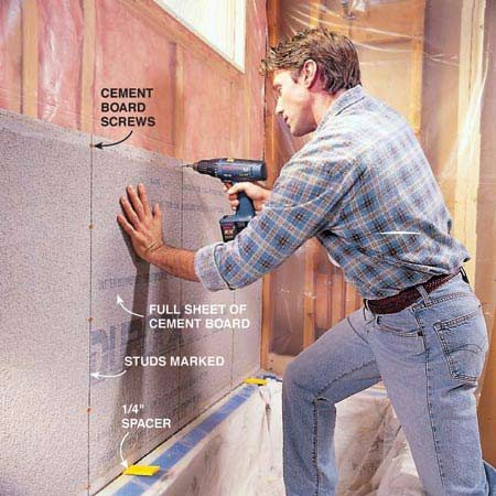 <b>Photo 4: Screw the board in place</b></br> Screw a full-size 3 x 5-ft. cement board to the back wall. Place special 1-1/4 in. cement board screws every 8 in. along each stud but 1 in. away from edges to avoid breakage. Hold the sheet above the tub shoulder with 1/4-in. spacers. Drive screws flush with the surface of the board, being careful not to break through mesh. Avoid driving them at an angle.