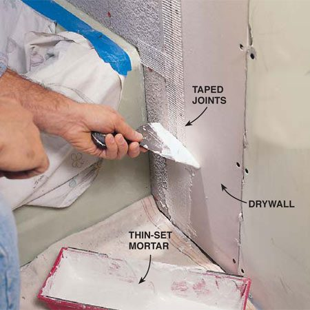 <b>Photo 12: Tape the seams with mortar</b></br> Cover the tape with a skim coat of thin-set mortar, squeezing it through the tape to fill voids and cracks. Remove any excess material before it hardens.