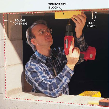<b>Photo 2: Attach a temporary block to hold the window upright</b></br> Screw a wood block to the underside of the sill plate. This temporary block will keep the glass panel from tipping inward, so make sure it extends down far enough to catch the upper edge of the panel. Many older homes have no sill plate. In that case, just screw the block to a joist.