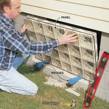 <b>Photo 3: Install the window</b></br> Set the glass panel in place with the bottom resting on two wedges cut from a 2x4. The bottom of the panel will tend to slide inward, so you must have a helper inside to steady the panel as you position it.