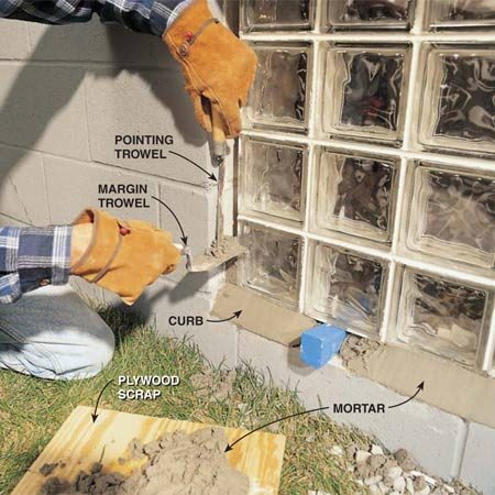 <b>Photo 5: Mortar along the sides of the panel</b></br> Pack mortar into the gaps under and alongside the panel. Pack the bottom and smooth the curb first, staying away from the wedges. Give the curb time to harden to the touch before you begin on the sides. That way, crumbs of mortar you drop can be brushed off the curb. Fill the gaps alongside the panel using your margin trowel and a pointing trowel.