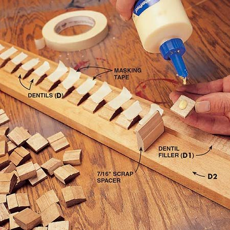 <b>Photo 8: Add the dentil molding</b></br> <p>Glue the dentil pieces (D) to the 1x4 backer board (D2), using masking tape to hold them as the glue dries. Parts D, D1 and D2 must be prestained before gluing. Allow the stain to dry at least a day so the glue will stick. The dentils are made from colonial-style stop that is first ripped to 1-1/8 in. then cut to 7/8-in. lengths. The filler piece at the top is the same uncut stop with the detailed side up. This piece will be hidden by the crown molding (J) later.</p>