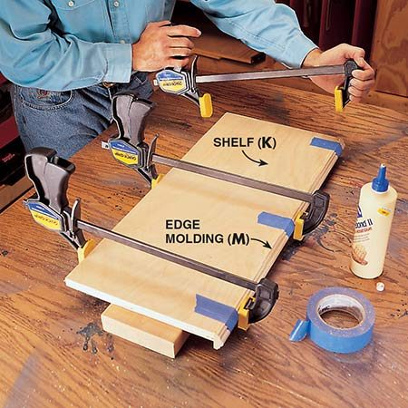 <b>Photo 9: Add edge molding</b></br> <p>Glue the edge molding (M) to the shelf (K). Use masking tape to align the molding and clamp it until the glue sets.</p>