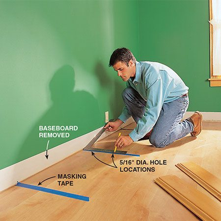 <b>Photo 10: Mark the standard locations</b></br> <p>Apply masking tape to the floor where the standards will be placed, then mark the hole locations for the pins (cut-off screws). Use a framing square as a guide to ensure that the holes will be perpendicular to the wall. Be sure to remove the baseboard.</p>
