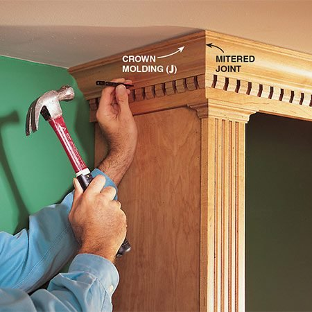 <b>Photo 16: Set the nails</b></br> <p>Set the nails after nailing the crown molding (J) into the filler strip (D2). Use 4d finish nails every 12 in. to nail the crown molding. (If you have a compressor and brad nailer, use that instead of hand-nailing.) Miter each end at the outside corner and butt the other ends against the wall.</p>