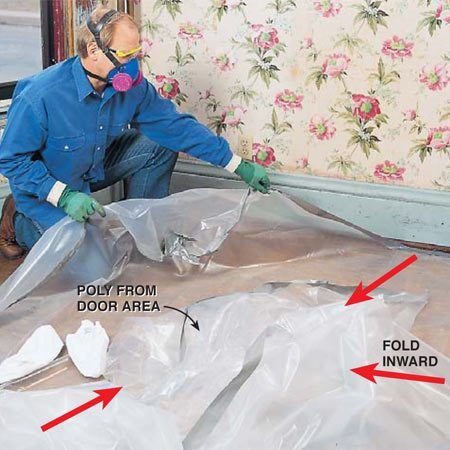 <b>Photo 14: Wet down the poly</b><br/><p> Wet down the contaminated surfaces of the poly with a spray bottle. Then fold the doorway poly inward, pull up the corners and fold them inward, and roll up the poly on the floor. Put the poly and other debris in 6-mil garbage bags and toss them into the trash.</p>