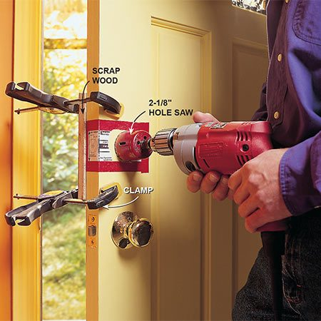 <b>Drill the cylinder hole</b></br> <p>Drill out the cylinder hole with the 2-1/8 in. hole saw. Use the same setback (distance from door edge to hole center) as the doorknob, either 2-3/8 in. or 2-3/4 in. After the hole saw's pilot bit pokes through the opposite side, remove the scrap wood protector and finish drilling the cylinder hole from the exterior side.</p>