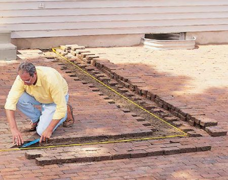 <b>Photo 2: Remove the pavers</b></br> <p>Remove the pavers to a width of about 1 ft. Stack the pavers neatly so you can later cut and replace them in the same slots. Then dig a trench 8 in. wide x 8 in. deep and fill it with crushed gravel. Level the gravel and tamp it smooth.</p>