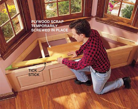 <b>Photo 1: Position the plywood</b></br> <p>Lay the tick stick across the scrap with the pointed end near the line that marks the front edge of the window seat. Trace a line onto the scrap along the side of the stick.</p>