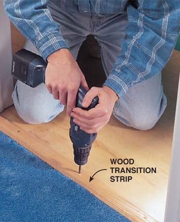 <b>Photo 10: Transition strip</b></br> <p>Seal the gap under a door with a door sweep and a transition strip. A wood transition strip covers the joint where two types of flooring meet and provides a ridge for the sweep to seal against. Metal strips don't work with sweeps because they aren't thick enough.</p>