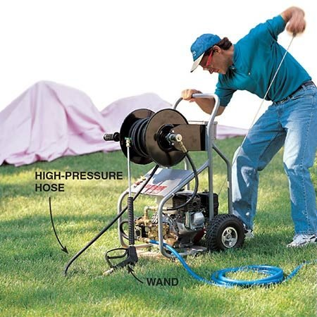 """<b>Photo 3: Hook up the pressure washer</b></br> <p>Connect the pressure washer to the outdoor faucet through an ordinary garden hose, attach a nozzle (see """"Selecting the Best Nozzle,"""" below) and start the engine. Wear goggles to keep paint chips and dirt out of your eyes, and clothing that can get soaked. You WILL get wet. Spread old sheets or painter's cloths on the ground and over shrubbery to catch paint chips.</p>"""