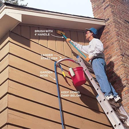 <b>Photo 10: Scrub inaccessible areas</b></br> <p>Clean high areas beyond the reach of the pressure washer extension with a scrub brush and a solution of detergent and TSP mixed in water. Begin from the lower areas and work upward, rinsing frequently. Keep the siding below damp so the TSP won't leave visible drip marks. When finished, rinse from the top down using a garden hose. An add-on ladder stabilizer makes the ladder more secure.</p>