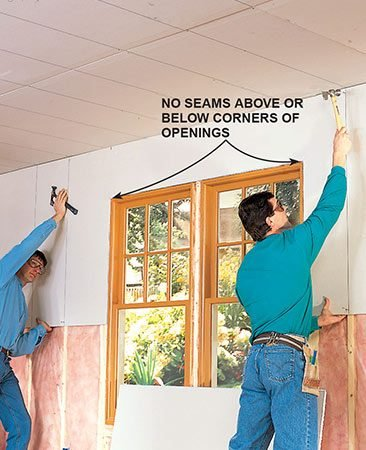 <b>Photo 7: Hang the sheet of drywall</b></br> <p>Lift the top wall sheet, holding it tight against the ceiling, and tack it into place with nails. Don't forget to mark fastener guidelines before lifting.</p>
