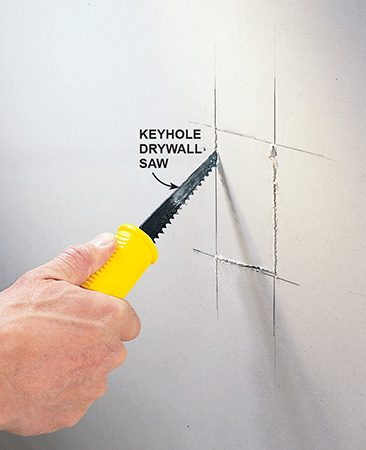 <b>Photo 9: Mark and cut the drywall</b></br> <p>Transfer measurements to the drywall and cut the outlet box openings with a keyhole saw.</p>