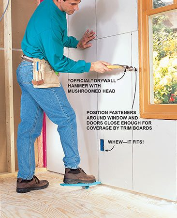 <b>Photo 10: Lever drywall into place</b></br> <p>Hoist bottom row with a foot lift or flat bar and tack into place. If an opening needs small adjustments, shave the edges with your utility knife.</p>