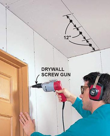 <b>Photo 11: Finish fastening with screws</b></br> <p>Screw ceiling and walls with a screw gun. Set screws and nails slightly below the surface of the paper, being careful not to break through into the gypsum core. To hide the fasteners, position them close to openings around windows and doors so trim will cover them.</p>