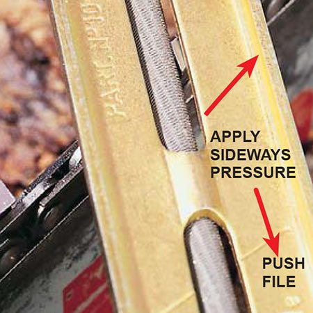 <b>Photo 5: Look through the file guide</b></br> Look through the file guide to line up the cutter with the file. You'll feel the file nest into the cutter. File every other cutter and then move to the other side of the bar to sharpen the rest.