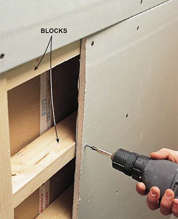 <b>Photo 2: Screw on the drywall</b></br> <p>Screw drywall to the blocks at butt joints. The drywall will bend inward slightly, creating a recess for the tape and mud.</p>