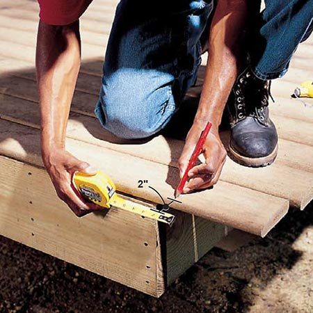 <b>Photo 16: Mark the cut line</b></br> <p>Measure 2 in. from the end joists and mark the decking for cutoff by snapping a line. The 2-in. overhang allows for the 7/8-in. thick cedar face board and a 1-1/8 in. overhang.</p>