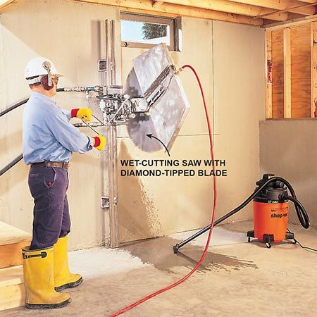 <b>Photo 7: Clean cuts through solid concrete</b></br> <p>This wet-cutting, track-guided saw can cut cleanly and completely through 12-in. solid-poured walls. The cost for hiring a pro to cut this egress window opening runs roughly $100 or more per hour, and the job will take three to four hours.</p>