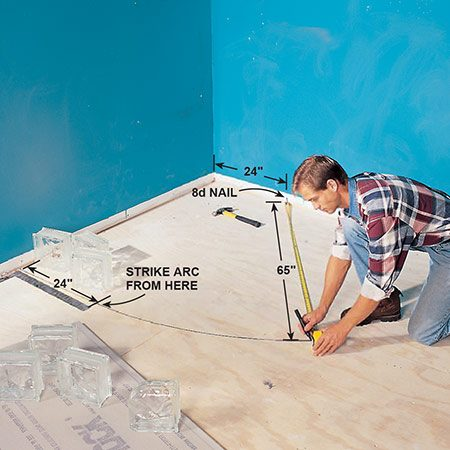 <b>Photo 1: Draw the floor</b></br> <p>Draw the outline of the shower floor on the subfloor to use as a pattern for setting the mortar forms. Nail an 8d nail next to the wall and strike a 65-in. arc for the curved form board.</p>