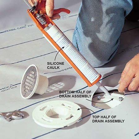 <b>Photo 8: Make a drain hole</b></br> <p>Cut out the vinyl liner for the drain with a utility knife, cutting just outside of the bolt holes. Run a bead of silicone caulk around the outer edge of the flange, then bolt down the top half of the drain assembly. Cover the top of the drain with duct tape to protect it during installation of the mortar bed and tiling.</p>
