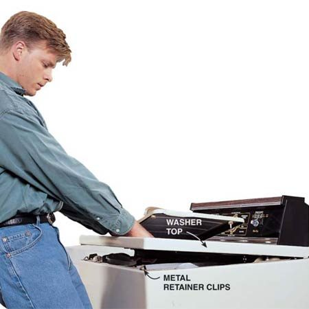 <b>Photo 3: Open the top</b></br> Lift the top of the washer by reaching through the lid and pulling the top toward you and up to disengage it from the metal clips. Then lift the top and tilt it back. Lean the top against the wall or support it with a length of chain or cord to keep it from falling too far back and straining the hinge clips.