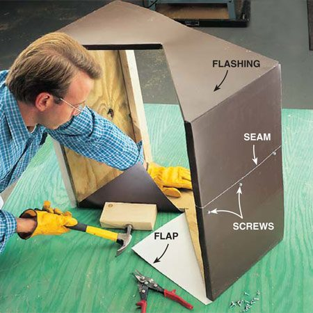 <b>Photo 14: Flash the saddle</b></br> Wrap flashing tightly around the saddle and fasten down the seam with self-tapping screws. To crease flashing around corners, use a hammer and wood block. When the saddle is wrapped, fold down the overhanging flashing along the top and bottom edges. At the V-notch, cut the flashing, fold the flaps into the saddle and secure each flap temporarily with one screw. All of this is a lot easier if you have a helper. And be sure to wear gloves—or plan to visit the emergency room for stitches!