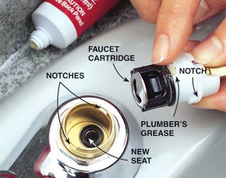 <b>Photo 3:  Install the new cartridge</b></br> Drop the new spring into the recess and push the new seat in with your finger. Spread a thin layer of plumber's grease around the cartridge. Push the cartridge into the faucet, aligning it with the notches. Then tighten the large retaining nut with the wrench and replace the handles.