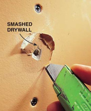 <b>Photo 2: Cut away loose material</b></br> Cut out crushed or damaged drywall with a sharp utility knife. Bevel the cut and don't leave any fuzzy bits of paper that would be hard to cover with the patching compound.
