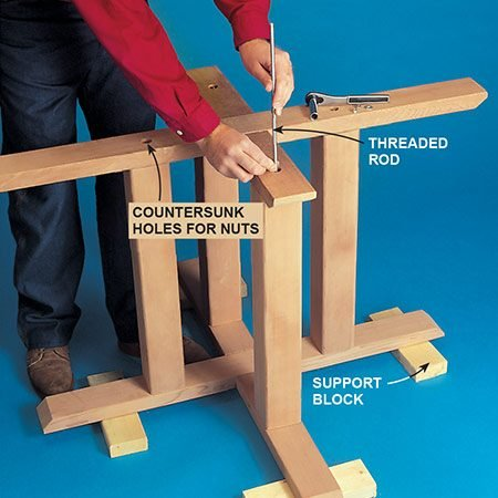 <b>Photo 4: Build the picnic table base</b></br> Assemble the base using threaded rod to hold it all together. <p>Putting the base up on blocks lets you attach the nuts and washers underneath.</p>