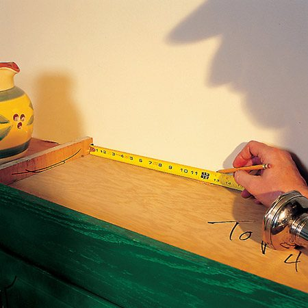 <b>Photo 6: Transferring the mark</b></br> <p>Measure the distance from the inside of the cabinets to the fasteners and then transfer the mark outside the cabinet by measuring from the side at the top.</p>