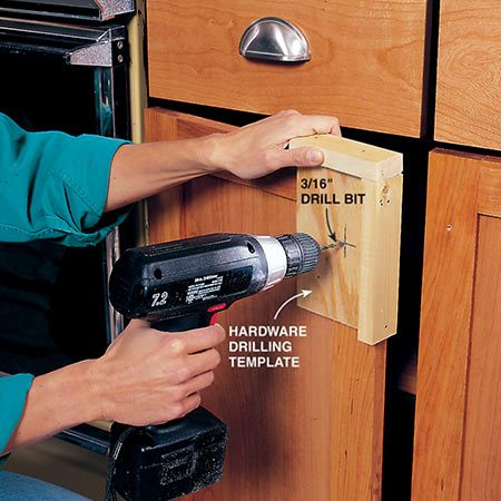 <b>Photo 17: Install new handles</b></br> <p>Install drawer pulls and doorknobs. Drill 3/16-in. holes for the knob screws. Use a template to accurately locate doorknobs. Measure carefully for drawer hardware. Use a sharp bit, high speed and medium pressure to avoid splintering the wood on the back of the hole. If splintering is a problem, clamp a small block of wood to the backside of the door before you drill the hole.</p>