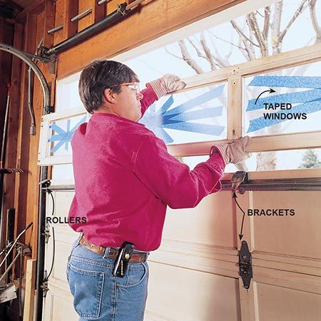 <b>Photo 2: Remove the old door</b></br> <p>Lower the door and dismantle it by removing the hardware. Lower a double door by recruiting at least two helpers to help with the weight, and place a 2x4 block under the door to prevent smashing a foot or finger when it's lowered. Remove the sections one at a time by disconnecting the rollers and brackets. If you have windows, tape them to help control flying shards if they break. Then remove the old roller tracks and remaining hardware.</p>