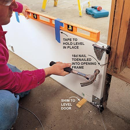 <b>Photo 3: Install the first section</b></br> <p>Center and level the first section after you install the brackets. The door must be level even if the floor isn't, so use shims under the section to level it. The rubber gasket on the bottom section will fill the gaps created by an unlevel floor. To hold the level in place, tape it to the section. To hold the section in place, lightly toenail a 16d nail into the frame and bend it over the section. Add brackets and rollers before setting them in place and stack one section on top of another, toenailing as you go up.</p>