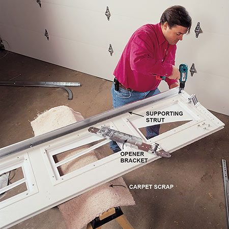 <b>Photo 4: Install the strut</b></br> <p>Install the stiffening strut on top of the top section of steel doors with the section lying flat. Then install the opener bracket that replaces the center bracket between the top two sections. While you're working on the sections, protect them from scratches by putting carpet scraps on top of your sawhorses. Now, slide the rollers into the roller brackets.</p>