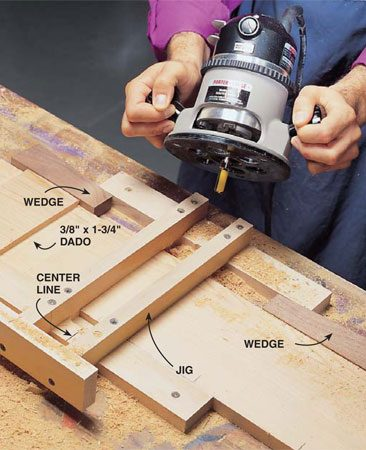 <b>Photo 1: Rout the dadoes</b></br> Lock your 1x6 workpiece into the jig (see jig dimensions below) with wedges. Be sure the jig is screwed to the workbench. Align the center mark of your lap joint with the center of the jig. Set the depth of your top bearing straight flute bit to make a 3/8-in. deep dado.