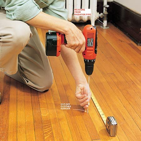 <b>Photo 1: Find a location</b></br> <p>Measure from a reference point, such as the radiator heating pipes shown, to locate the floor outlet so it falls between the 2x10 floor joists. Then use an 8-in. straight length of clothes hanger, snipped off at an angle to form a point, as a locator bit. Start the drill slowly while holding the hanger to keep it from whipping around as you drill through the flooring.</p>