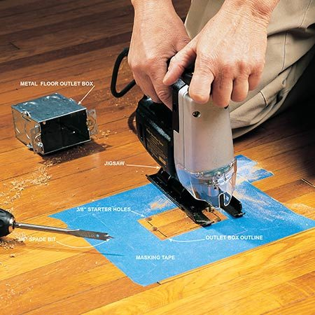 <b>Photo 3: Cut a hole for the box</b></br> <p>Outline the outlet box on the floor. Drill two 3/8-in. holes at the corners where the screws protrude from the sides of the metal box and two more where the outlet mounting screws go. Now use a jigsaw with a wood-cutting blade to complete the box cutout. Apply masking tape to protect the floor finish.</p>