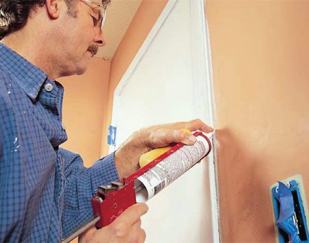 <b>Photo 7: Caulk the gaps</b></br> Caulk all wall/woodwork joints with a paintable white silicone/latex caulk. Cut a small (1/8-in.) hole in the end of the nozzle. Wipe off excess and smooth caulk beads with a damp synthetic sponge.