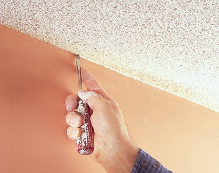 <b>Photo 8: Create a flat edge</b></br> Drag a flat screwdriver over the edges of ceilings to remove a thin line of texture. This will ensure crisp paint lines later when you're cutting in the wall paint along the ceiling.