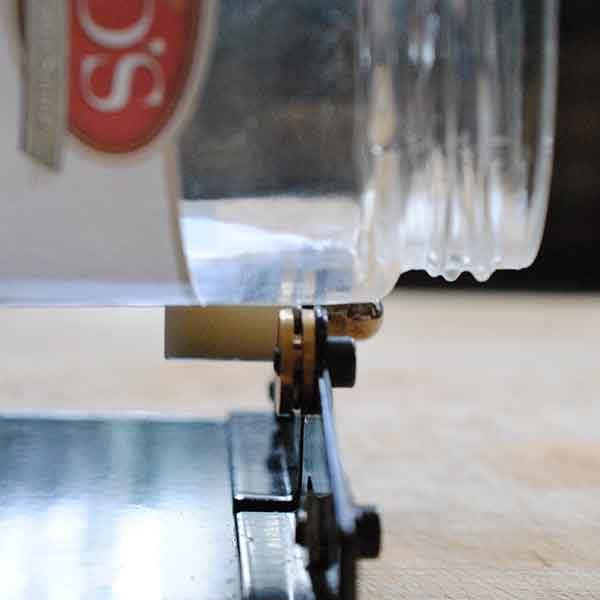 <b>Rotate the bottle to create a score line</b></br> <p> Check the score line on the bottle; it should be a faint white line that goes all the way around the object. If any section of the line is missing or too thin, the bottle will not break properly, so put it back into the cutter and score it again. Ideally, you should score the object only once, but you might have to practice a few times to get the hang of it.</p>