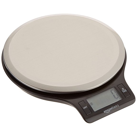 Circular scale with 'Amazonbasics' written above the display screen on the front. The top of the scale is a light gray and the bottom black