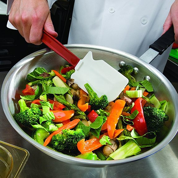 Red spatula being used to stir a skillet full of sliced veggies over a metal counter